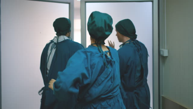 vidéos et rushes de back view of emergency doctor team run on walk way in hospital - operating