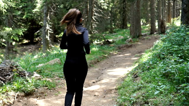 back view of female athlete who run on a mountain trail