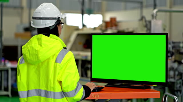 4k back view of female industrial engineer using a computer with green screen monitor working in a heavy industry manufacturing factory - manufacturing machinery stock videos & royalty-free footage