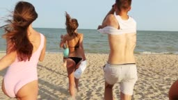 Back view of group of friends undress running into the sea water on sunset and throw shirts on the beach. Cheerful happy people having fun on the beach. Men and women go to swim in slow motion