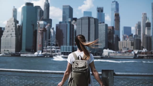 Back view of happy female tourist with backpack raising arms wide open at New York skyline view, looking back at camera