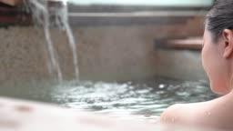 back view of Japanese girl soak in hot springs