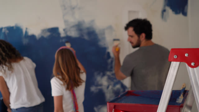 back view of latin american young family painting a wall with blue at home - bricolage video stock e b–roll