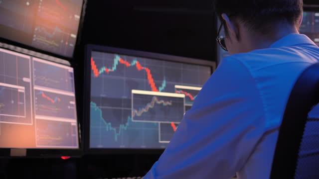 vídeos de stock, filmes e b-roll de visão de trás dos empresários asiáticos de liderança sentados à mesa com monitores de computador mostrando gráficos de linha e análise, encontrando solução à noite de trabalho até tarde. trabalhando conceito tardio. - habilidade