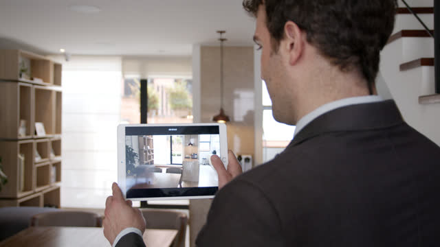 back view of male realtor recording a video of a house to promote sales online using a tablet - loft apartment stock videos & royalty-free footage
