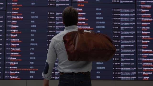 stockvideo's en b-roll-footage met back view van de mens op de luchthaven die zijn bagage terwijl u kijkt naar de vluchtschema scherm - vluchtschema