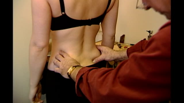 back view of osteopath examining and manipulating back of female patient zoom in - osteopath stock videos & royalty-free footage