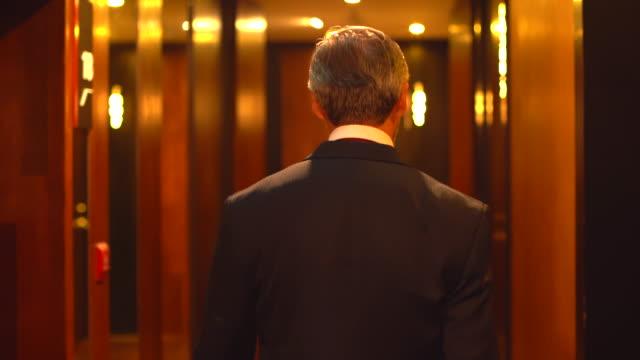 オフィスを歩いている先輩ビジネスマンのバックビュー。オフィスを歩くブリーフケースを持つビジネスマン。ブリーフケースでビジネスマンの足をフォローアップします。 - 副代表点の映像素材/bロール