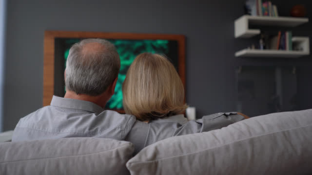 back view of senior couple relaxing on couch watching tv very comfortable - rear view stock videos & royalty-free footage