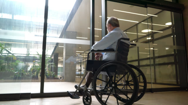 back view of senior man on wheel chair at a nursing home looking through glass door - wheel stock videos and b-roll footage
