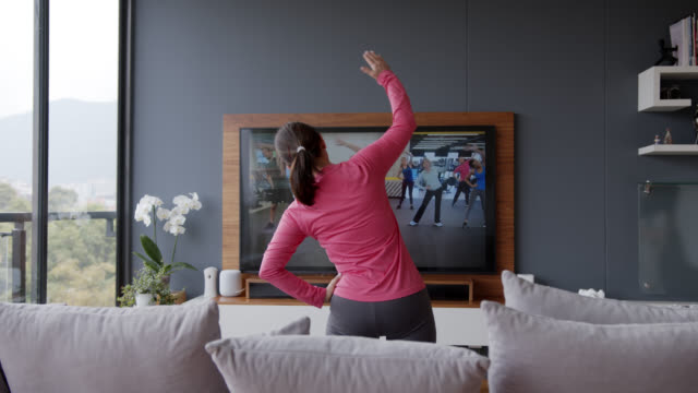 back view of senior woman following an online stretching class looking at tv screen - moving after stock videos & royalty-free footage