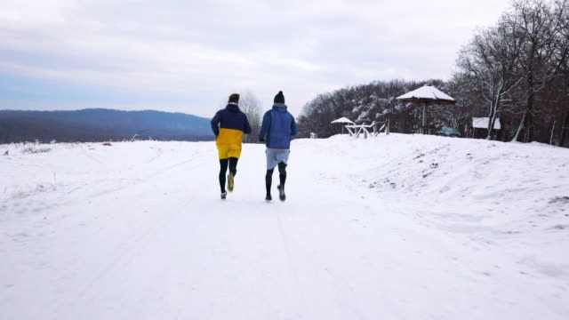 Rückansicht des sportlichen Herren jogging auf dem Schnee.