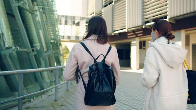 stockvideo's en b-roll-footage met achtermening van twee vrouwen die op campus lopen - sunny