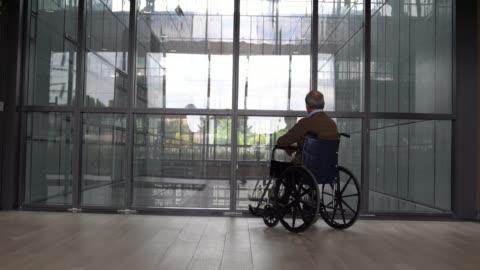tillbaka syn på oigenkännlig senior man på rullstol på ett ålderdoms hem - oigenkänliga personer bildbanksvideor och videomaterial från bakom kulisserna