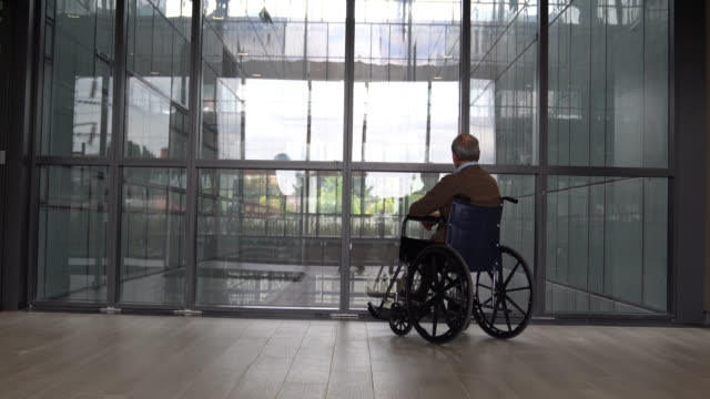 back view of unrecognizable senior man on wheelchair at a retirement home - unrecognizable person stock videos & royalty-free footage