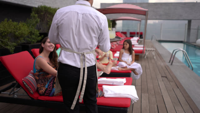 back view of waiter taking lemonade to couple with their kids at the hotel rooftop pool all looking very happy - getting away from it all stock videos & royalty-free footage
