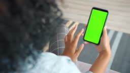 Back view of woman brunette using green screen smartphone touching screen
