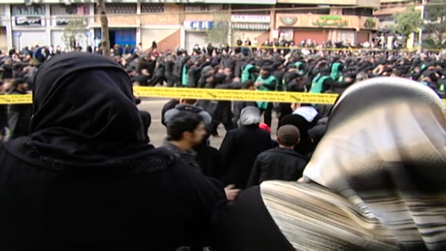 back view of women watching shiite men performing ritual chest beating to the rhythm of a chant at an ashura procession in dahieh, organised by... - rhythm stock videos & royalty-free footage