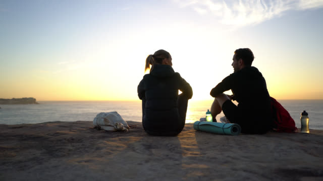 back view of young caucasian couple enjoying the sunrise sitting on cliff talking - emotion stock videos & royalty-free footage