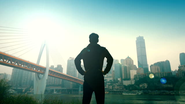 Back view of young man looking cityscape view