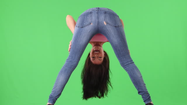 Back view of young woman in tight jeans bending over and smiling
