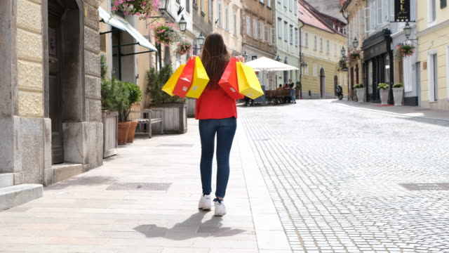 back view shot of a girl walking up the street with shopping bags - shopaholic stock videos & royalty-free footage