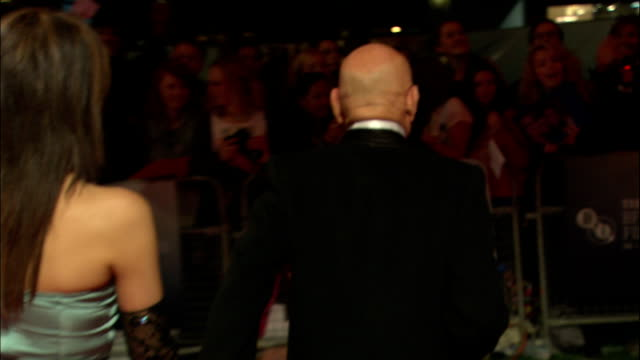 back view MS Sir Ben Kingsley walks over to sign autographs for fans behind barricades with wife Daniela Lavender following behind