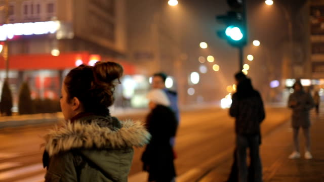 Back view. The sad young brunette girl is waiting the green light to cross the road