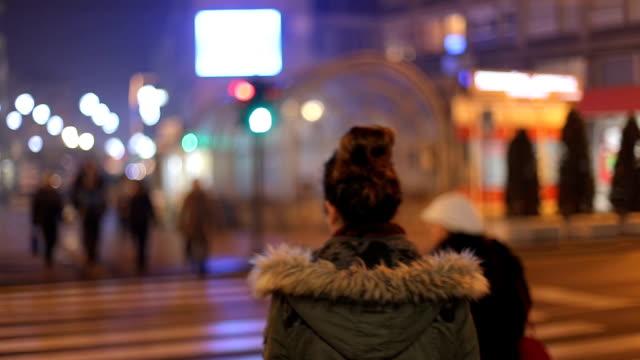 hinten sie ansicht von. das traurige junge brünette mädchen wartet grünes licht für die straße zu überqueren - crossing stock-videos und b-roll-filmmaterial