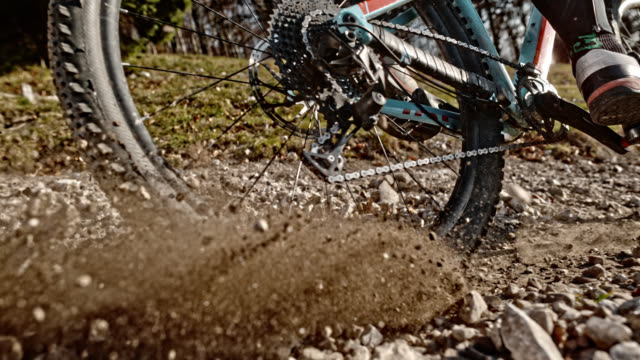slo mo back wheel of mountain bike pushing gravel into the air in sunshine - gravel stock videos & royalty-free footage