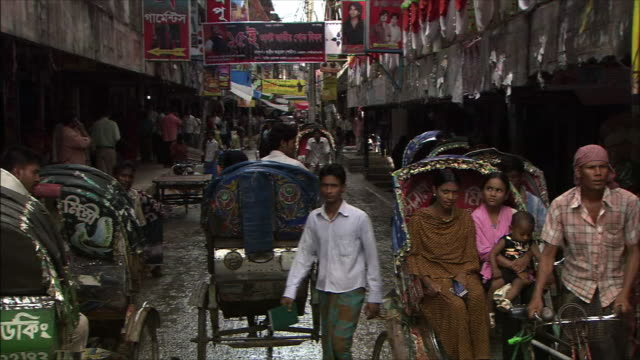 Pan Right Street facing the river Rickshaws and people come and go