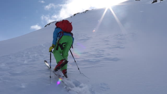backcountry skier ascends snow slope towards summit - ski jacket stock videos & royalty-free footage