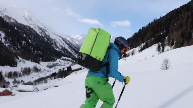 backcountry skier ascends snow slope with heavy pack - ski jacket stock videos and b-roll footage