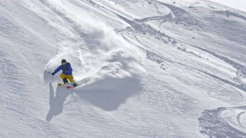 slo mo backcountry skier descending the mountain in sunshine - warm clothing stock videos & royalty-free footage