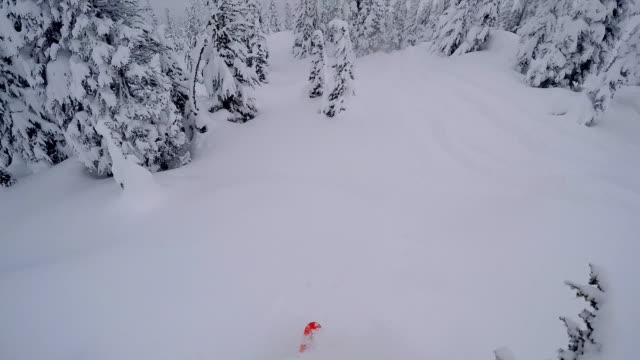 Backcountry skier descends from a snowy ridge in mountains