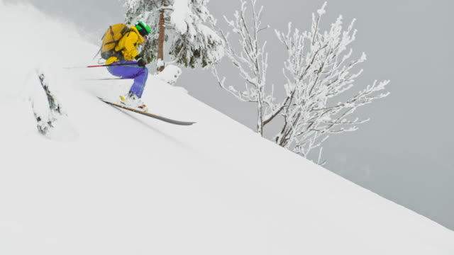 slo mo backcountry skier doing a jump in powder snow - powder snow stock videos and b-roll footage