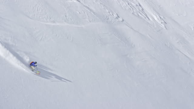 slo mo backcountry skier skiing down the mountain in sunshine - powder snow stock videos and b-roll footage