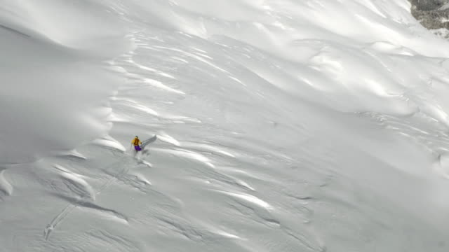 AERIAL Backcountry skier skiing down the sunny mountain slope