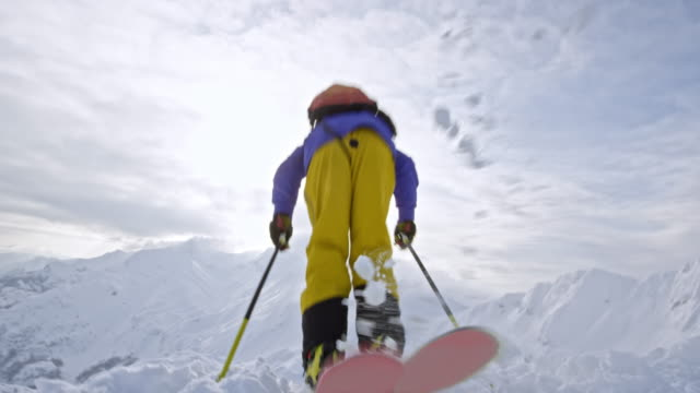 backcountry skier stepping into bindings and skiing away - moving down stock videos and b-roll footage