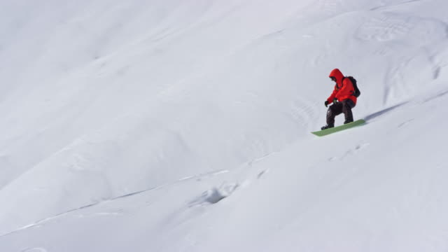 SLO MO Backcountry snowboarder riding down the slope in sunshine
