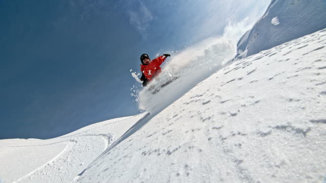 SPEED RAMP Backcountry snowboarder splashing powder snow into the camera