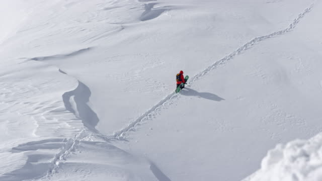 slo mo ld backcountry snowboarder walking up the snowy mountain - snowboard stock videos and b-roll footage