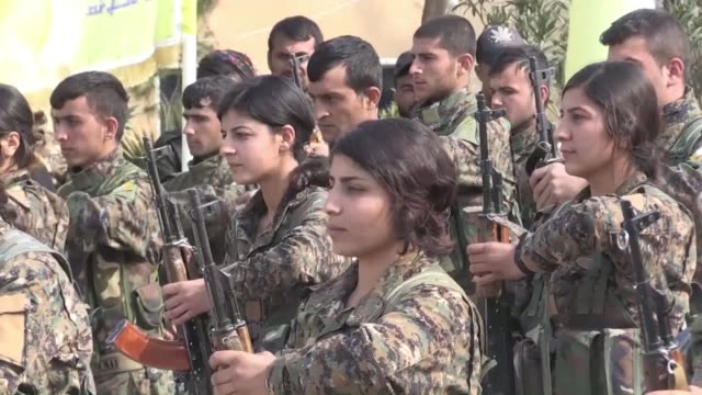 backed kurdish led syrian democratic forces fighters attend a ceremony in tribute to their comrades killed during battles with the islamic state... - militante gruppe stock-videos und b-roll-filmmaterial