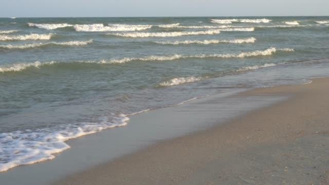 Bakgrunden tom sanden och vågorna