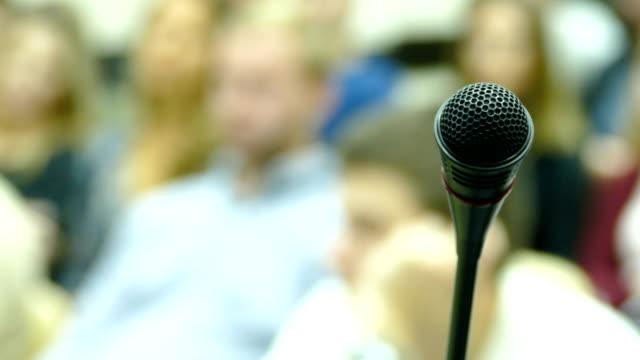 hintergrund - mikrofon auf einem hintergrund von menschen - tribune tower stock-videos und b-roll-filmmaterial