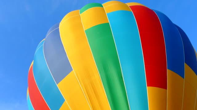 vídeos de stock e filmes b-roll de background - multicolored balloon on the sky background - encher atividade