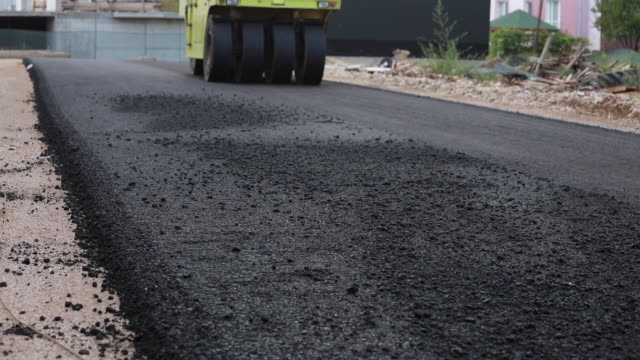 background of asphalt roller that stack and press hot asphalt - driveway stock videos & royalty-free footage