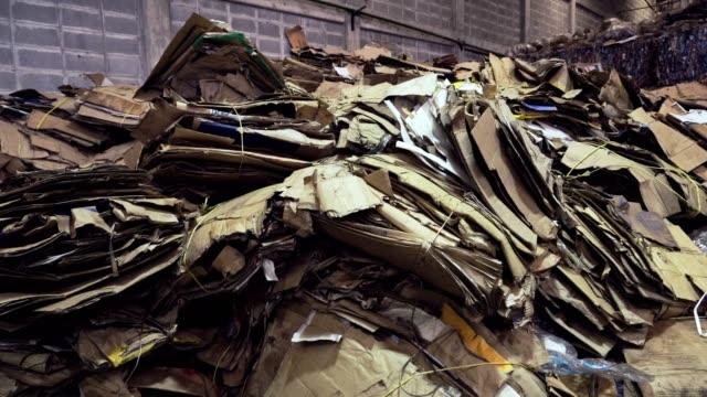 リサイクルセンターでプロセスを待っている砕いた段ボール杭の背景。 - ゴミ捨て場点の映像素材/bロール