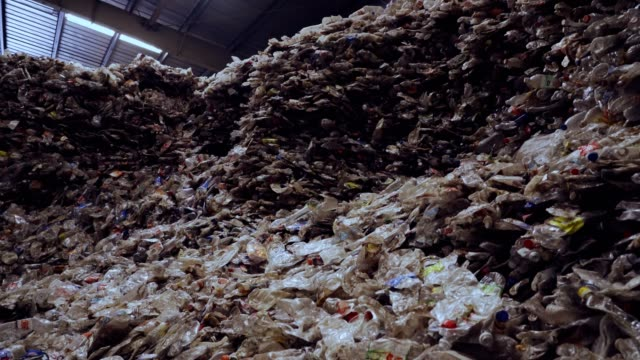 background of crushed clear plastic bottles pile waiting for process in a recycling center. - hay bail stock videos & royalty-free footage