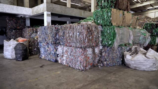 background of stack cubes of crushed clear plastic bottles waiting for process in a recycling center. - bundle stock videos & royalty-free footage